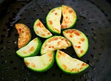 ズッキーニをフライパンで焼いている画像